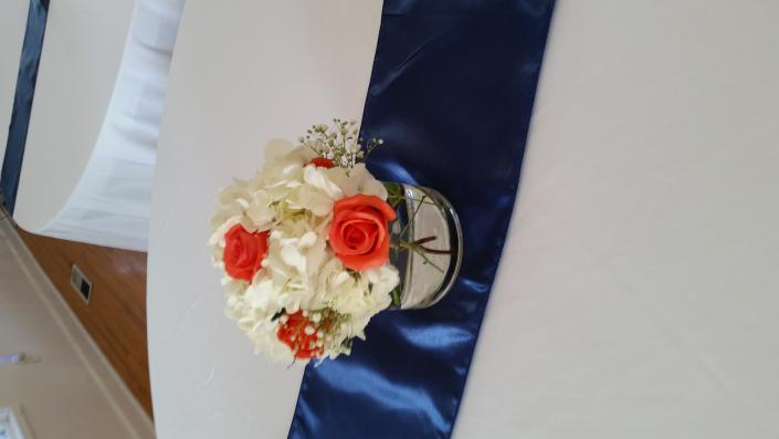 Little hydrangea centerpiece with coral roses on a navy table runner