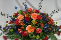 FOREVER TREASURED  Half Casket Spray of Seasonal shades of peach, reds, blues and lime greens. Roses, gerbera daisies, blue delphinium, button poms and more.