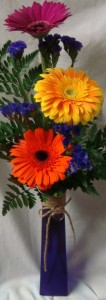 3 Large Gerbera Daisies with filler in tall cute colored vase with a heart and raffia ribbon.