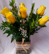 6 bright yellow roses with wax flower or baby's  breath depending on season.