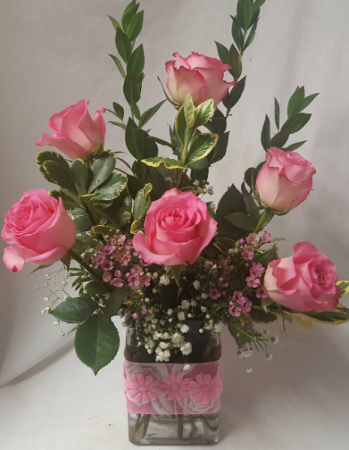 6 PINK ROSES ARRANGED IN A FABRIC COLOR WRAPPED RECTANGULAR VASE.