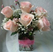 6 Pink Roses arranged in a vase with Baby's Breath in a cute rectangular vase with pink and white ribbon detail on vase.