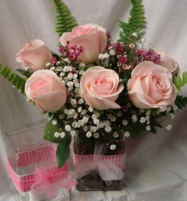 6 Pink Roses in a cute ribbon detail vase with baby's breath and wax flowers.