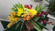 A warm and tropical sympathy spray Casket spray