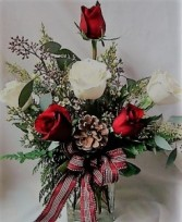 3 WHITE ROSES AND 3 RED ROSES ARRANGED IN A CUBE VASE WITH CHRISTMAS GREENS, CHRISTMAS BOW AND PINECONE.