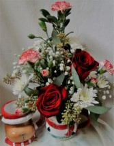 Holiday mug with red roses, white poms ,peppermint carnations and christmas greens arranged.