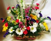 EUROPEAN GARDEN TRIBUTE Seasonal mixed bright flowers in wicker basket