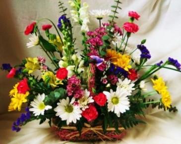 EUROPEAN GARDEN TRIBUTE Seasonal mixed bright flowers in wicker basket