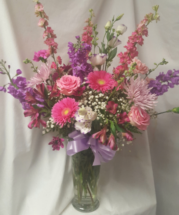 BEAUTIFUL MIX OF PINKS, LAVENDERS,  and purple flowers arranged in a vase with filler. We will select seasonal flowers.