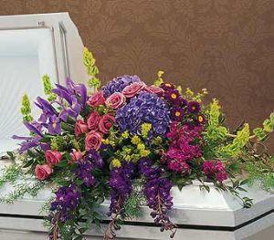 FOND REMEMBRANCE Half Casket Spray of purple delphinium, iris, bells of ireland, hydrangea, roses and more.