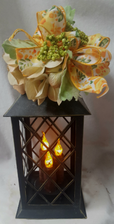 Rustic looking Tin lantern with LED lights Batteries included with seasonal silk flowers and bow(silk may vary)