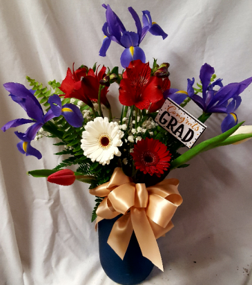 Talawanda Graduation colors! Red, white and blue  flowers arranged in a blue or red mason jar. (The blue flowers could be a Iris or Delphinium and the red and white flowers could change just depends what's n stock)