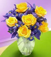 BRIGHT SMILES!! 6 yellow roses with blue iris arranged in a clear vase!!