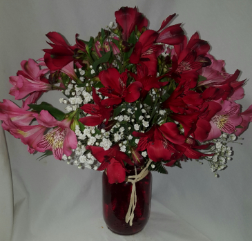 """Home Grown Little Miami Lilies"" arranged in a  Colored Mason Jar with baby's breath and raffia ribbon around jar. (Colors may be substituted if red and pink lilies are not available."