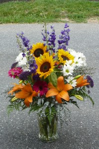 Garden Mix of Sunflowers, Daisies, Lilies, Delphinium, in Glass Vase Shown at $125.00
