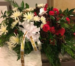 Christmas Casket Spray Christmas Green, White and Red Flower, accented with Pine Cones and Coffee Beans in Plainview, TX | Kan Del's Floral, Candles & Gifts