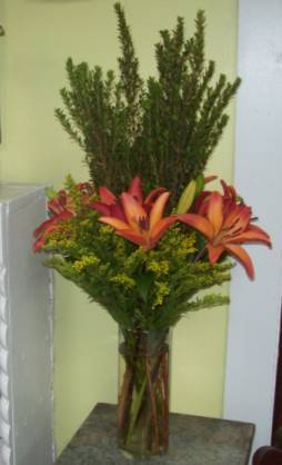 Contemporary Lilies cylinder vase of lilies with center of tall greens in a bed of Salidago