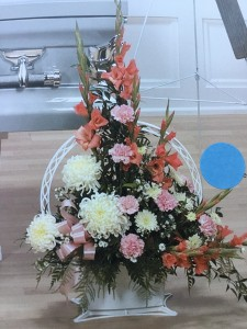 Coral glads, pink carnations, white mums Funeral arrangement