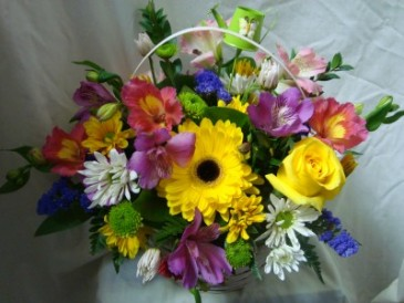 IN MEMORY ARRANGEMENT Take home arrangement after services. Mixed seasonal flowers in a basket.