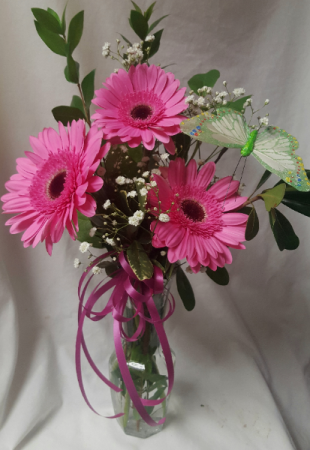 3 PINK GERBERA DAISIES WITH BOW AND BUTTERFLY IN A BUD VASE.