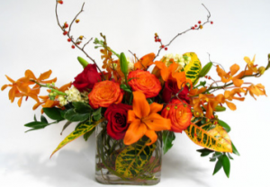 Fall in the Tropics Red & Orange roses, lilies and oncidium orchids and foliage in Monument, CO | ENCHANTED FLORIST