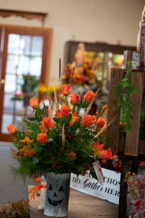Fall Roses in jack-o'-lantern container  in Vincennes, IN | ORGAN FLORIST & GREENHOUSES
