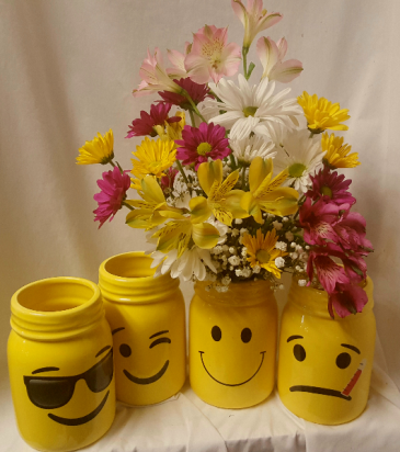 MASON JARS WITH FACES...WE WILL SELECT WHAT IS IN  stock with the smiley versions. If you want the one for a get well just put that in the additional information area and we will select that one. ARRANGED with bright colored daisies, filler and astramaria lilies.
