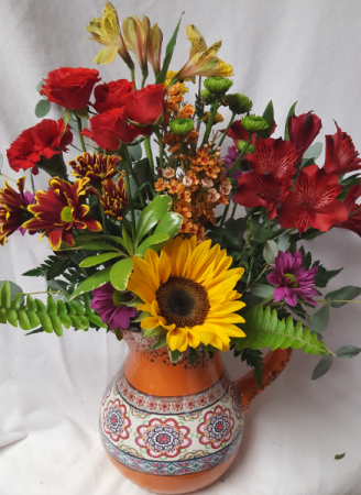 FIESTA PITCHER arranged with bright seasonal Flowers. (Pitchers may vary in color) Great keepsake container!!!
