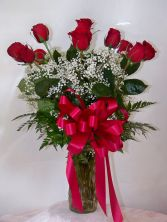FOREVER YOUNG ROSES Classic dozen red roses in vase with filler, greens, and bow.