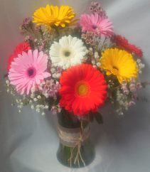 Large Gerberas arranged in a vase with filler and wax flowers.