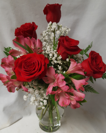 """Red roses and pink lilies""arranged in a Vase with baby's breath or wax flowers."