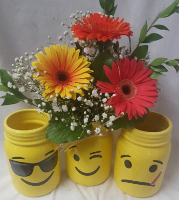 """EMOTION EMOJI MASON JAR ARRANGEMENT"" 3 LARGE  GERBERA DAISIES WITH FILLER IN THE WINK FACE MASON JAR. (GERBERA COLORS MAY CHANGE) Will send get well or sunglass face if you specify in additional information area."