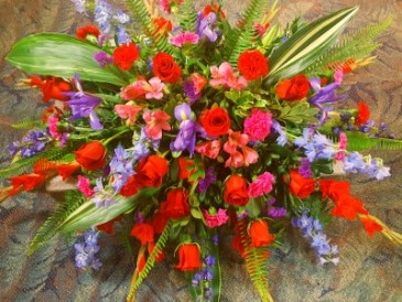 LOVING THOUGHTS Half Casket Spray of shades of blues, reds and purples. Roses delphinium, carnations, alstroemeria lillies, and more