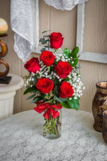 Half dozen red roses roses in vase with babies breath, greens