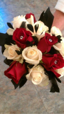 Hand Held Red and White roses with feathers and stones.