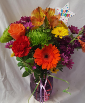 HAPPY BIRTHDAY CELEBRATION BOUQUET...Colored vase  with colorful seasonal flowers arranged with a Happy Birthday Pick!!