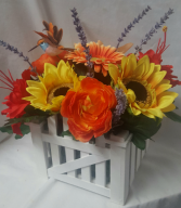 SILK BRIGHT FLOWERS ARRANGED IN WHITE Picket  fence looking wood container. ARRANGED all the way around to make a nice centerpiece. Great for funerals, nursing centers, etc. With hummingbird too!
