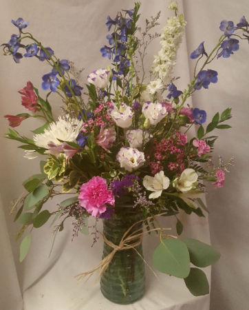 Large vase arrangement with shades of purples, blu and whites.