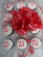 Yummy!! Dozen chocolate cupcakes with white  buttercream icing with red 21 on them!! Need 30 hours notice for delivery.
