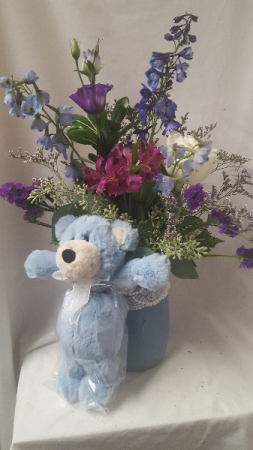 Boy Pearls and Lace Mason jar filled with shades  of blues, purples and whites and blue bear attached. Flower choices may vary depending on stock and seasonal.