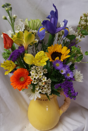 Ceramic pitcher with raffia  wrapped handle filled With bright mixed seasonal flowers! (Pitcher colors may vary)