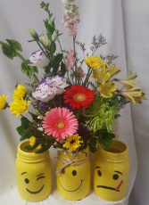 NEW!!Cute bright yellow mason jars with smiley,  and get well FACES. We will select the smiley or wink face if card is not about someone sick. If card is saying Get Well we will select that one. Flowers will be bright and cheery. May look different according to stock.