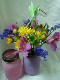 "Small mason jar arrangement of a small assortment  of flowers. Cute pick me up and nice keepsake jar and cute hummingbird pic. (approx. 12"" x 7"")"