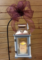 lighted lantern  on stand with bow