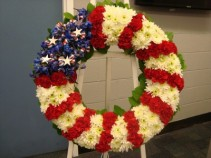 Red, White and Blue wreath with white Easel stand. Carnations, delphium and white cushion poms with ribbons and stars.