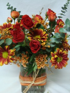 Orange and Red spray Roses with fall varigated daisies and wax flower all arranged in a rectangular vase!