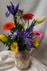Mason Jar with lace filled with bright flowers. (mason jar color may vary)