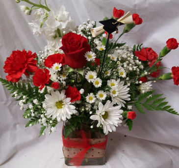 Miami congratulation arrangement a pic that has a  hat and diploma. This Arrangement will have different Reds and white flowers.