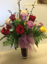 Mixed colour roses in vase  Vase arrrangement .
