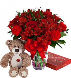 """""""SWEET SURPRISE"""" RED FLOWERS ARRANGED IN VASE...   INCLUDED WITH THE FLOWER ARRANGEMENT WILL BE A TEDDY BEAR AND A BOX OF CHOCOLATES! BEAR AND BOX OF CHOCOLATES INCLUDED IN ALL THE PRICE RANGES."""